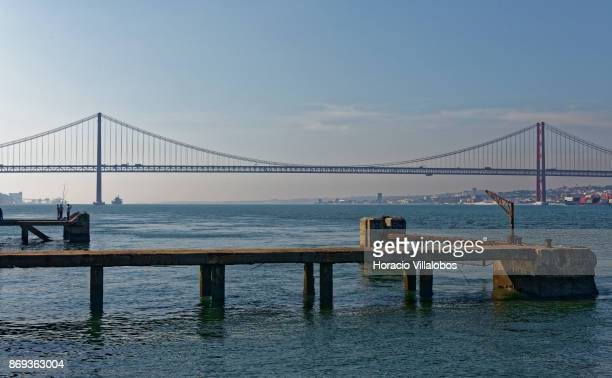 Fishermen at the end of a pier by the Tagus River and 25 de Abril Bridge are seen on October 31 2017 in Cacilhas Portugal Although active all year...