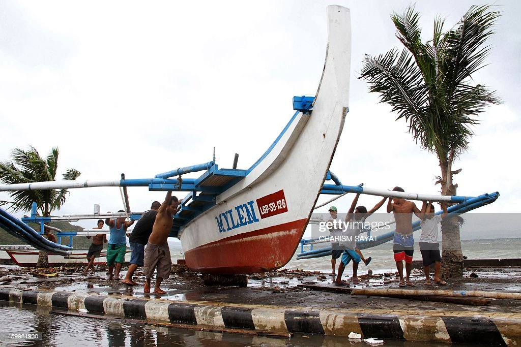 Fishermen carry thier outrigger to higher ground in Legazpi City south of Manila on December 5 ahead of the landfall of Typhoon Hagupit Thousands of...