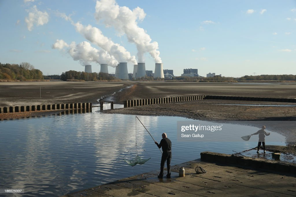 Fishermen cast nets as the cooling towers of the Jaenschwalde coal-fired power plant loom behind on October 31, 2013 in Peitz, Germany. The Jaenschwalde plant is fed with lignite coal from nearby open-pit mines, and according to plans by Swedish energy conglomerate Vattenfall and approved by the Brandenburg state legislature, at least five local communities are to be raized and their inhabitants compensated and relocated in order to make way for the expansion of a nearby mine. Energy policy and the role of coal is a heated topic at the moment in coalition negotiations between the Social Democrats (SPD) and Christian Democrats (CDU) currently taking place in Berlin.
