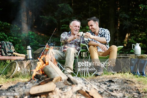 Fishermen drinking coffee beside bonfire : Stock Photo