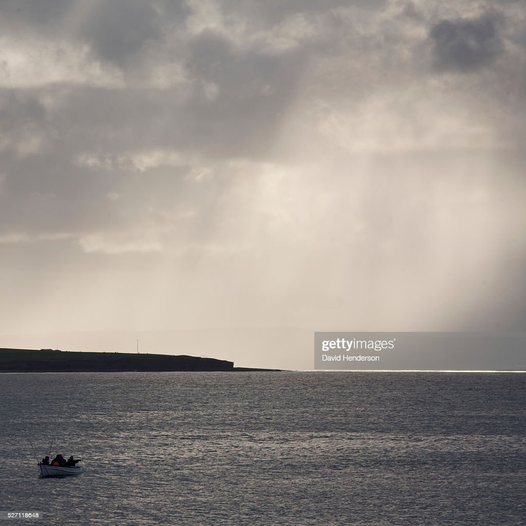 Fishermen escaping storm in small boat : Stock Photo
