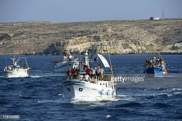Fishermen escort the boat of the pontiff leaving Lampedusa island to cast a wreath into the sea in memory of migrants who have drowned trying to...