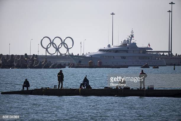 Fishermen fish from a quay near the Olympic rings logo and the seaport in Sochi Russia on Monday May 2 2016 The ruble weakened the most among...