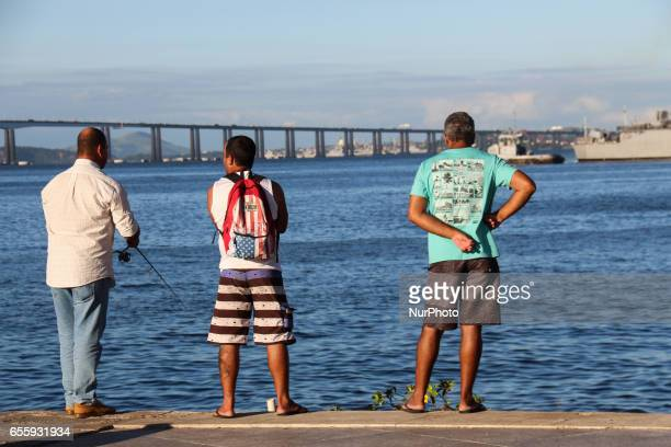Fishermen fish in the polluted waters of Guanabara Bay Early fall in Rio de Janeiro Brazil is marked by a sunny day with pleasant temperatures in the...