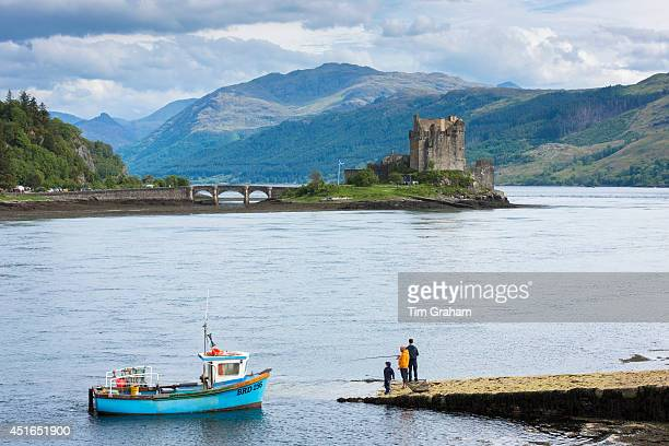 Fishermen fishing by Eilean Donan Castle a highland fortress in Loch Alshe at Dornie Kyle of Lochalse in the western hIghlands of Scotland