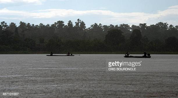 Fishermen from Peru's Amazonian region row their Pequepeque boats onomatopoeic name given for the sound of their motors in the Pastaza River in...