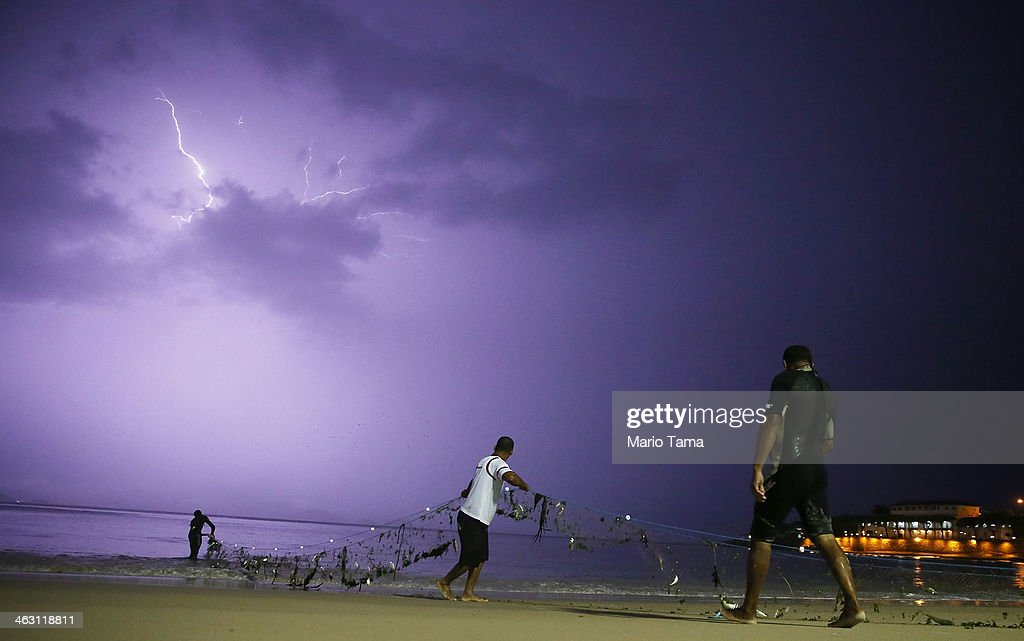 Fishermen gather their net along Copacabana Beach as lightning flashes during a powerful early evening thunderstorm on January 16, 2014 in Rio de Janeiro, Brazil. Heavy rains flooded some streets and caused power outages in certain neighborhoods.