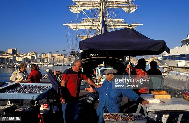 Fishermen go about their daily business at the fishing port against the backdrop of the threemasted sailing ship the 'Belem'