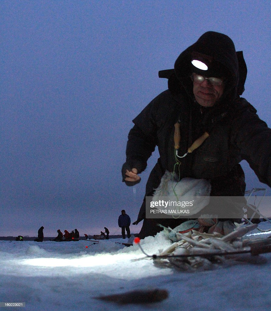 A fishermen kneels on the frozen surface of the Kursiai Lagoon near Klaipeda, Lithuania, to catch smelts on January 27, 2013. Several thousands of amateur fishermen from all over Lithuania gather on the ice to catch the small fish. AFP PHOTO / PETRAS MALUKAS