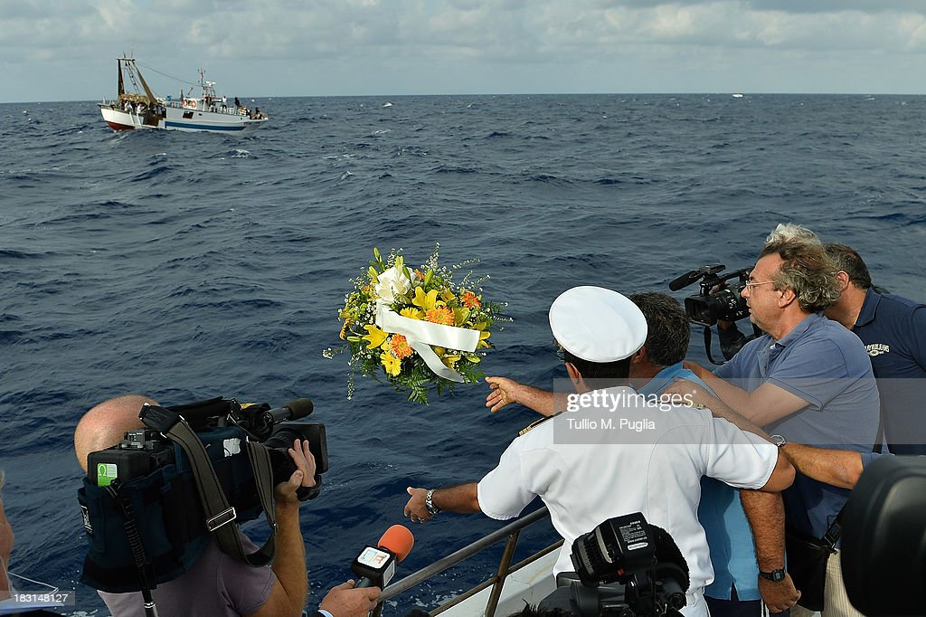 Fishermen lay a wreath in memory of victims of a immigrants disaster over the Lampedusa shore on October 5 2013 in Lampedusa Italy The search for...