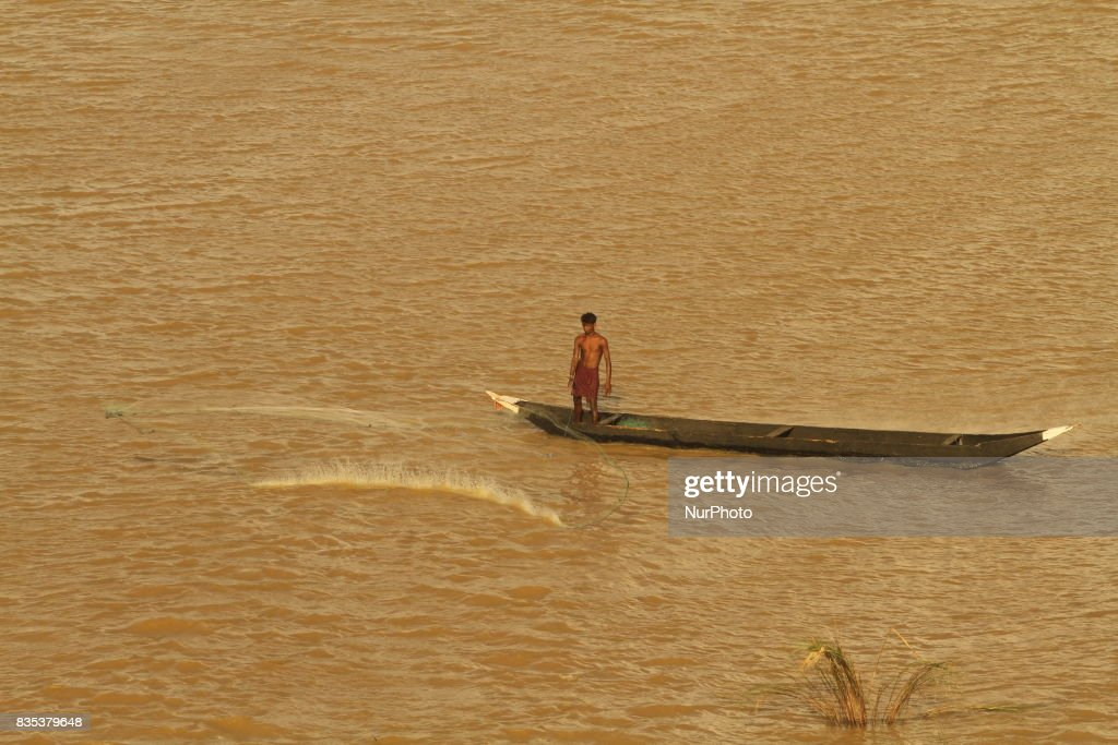 Fishermen look at a fishing country boat as they prepares them for fishing inside the Mahanadi river outskirts of the eastern Indian state Odisha's capital city Bhubaneswar on 19 August 2017.