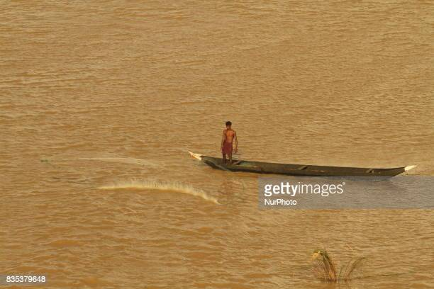 Fishermen look at a fishing country boat as they prepares them for fishing inside the Mahanadi river outskirts of the eastern Indian state Odisha's...