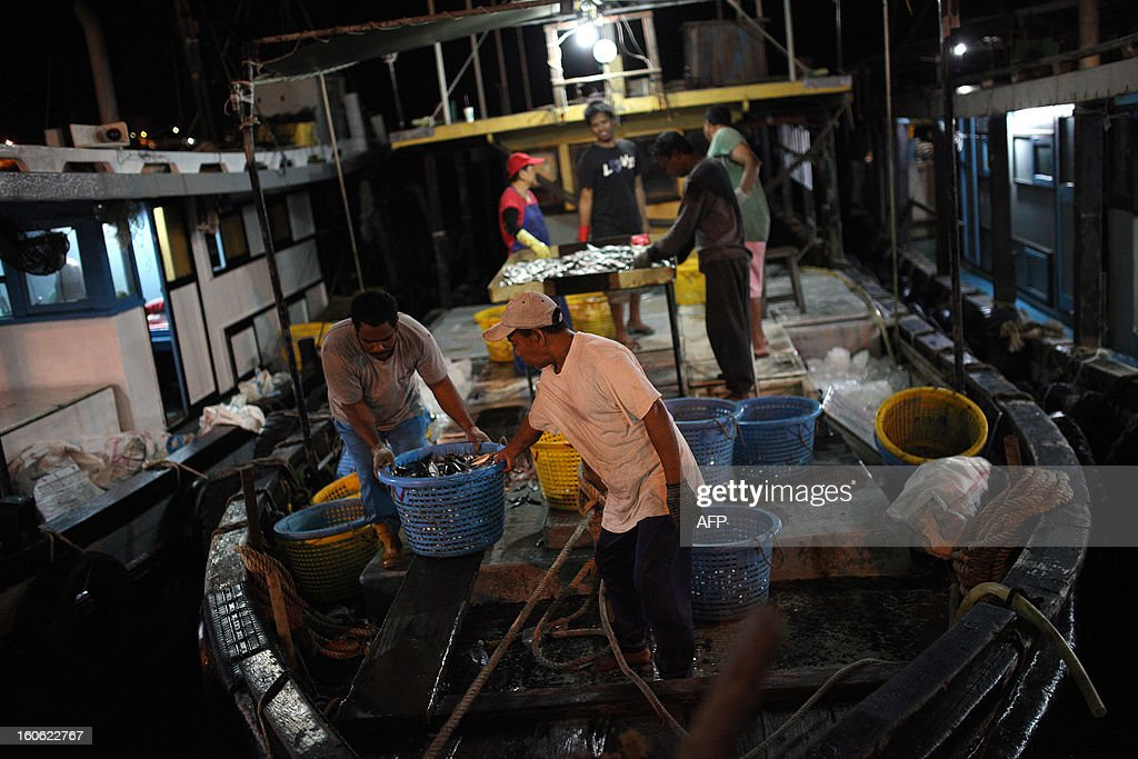 Fishermen off load their catch from a boat at the Sandakan central fish market in the Malaysian Borneo state of Sabah on February 4, 2013. Sandakan is the second-largest city in Sabah, eastern Malaysia, on the northeastern coast of Borneo. AFP PHOTO / MOHD RASFAN