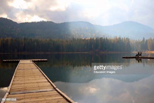 Fishermen on a dock with the reflections and light fog of the calm lake at Round Lake State Park in the panhandle of northern Idaho Round Lake State...