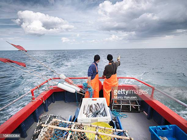 Fishermen on boat pointing out to sea
