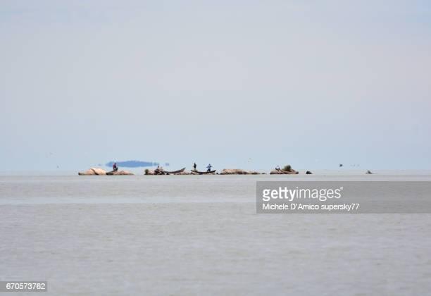 Fishermen on far rocks in Lake Victoria, in front of Entebbe.