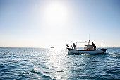 Fishermen on fishing boat at sea