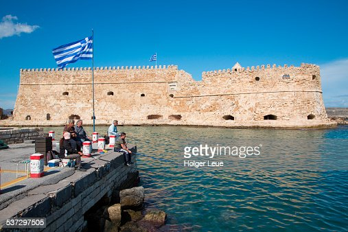 Fishermen on pier and Koules Fortress