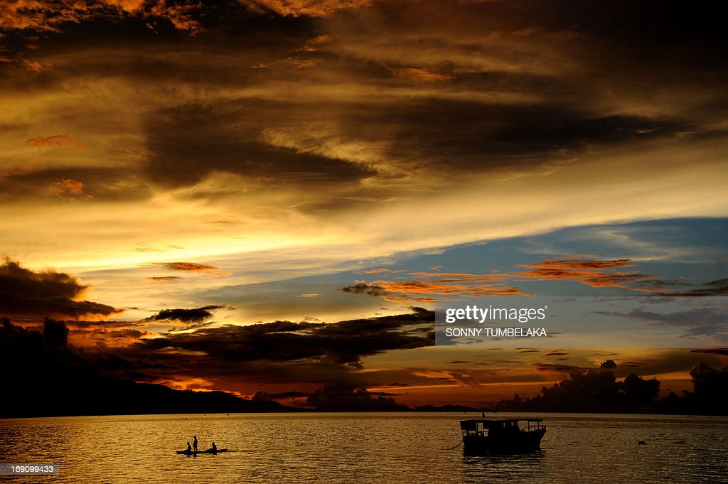 Fishermen (L) paddle a traditional boat during sunset at Waiara beach in Maumere on Flores island in East Nusa Tenggara on May 20, 2013. The Indonesian government has set the ambitious target of welcoming a total of nine million foreign tourists in 2013 increasing to 10 million by 2014.