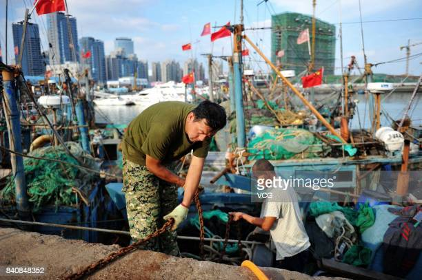 Fishermen prepare fishing gears at a fishing port on August 30 2017 in Qingdao Shandong Province of China Fishing ban started from May 1 on China's...