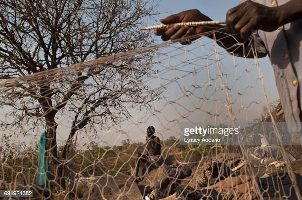 Fishermen prepare their nets in Southern Sudan near the Ugandan border February 6 2008 Villagers continue to be living in the bush in fear of...
