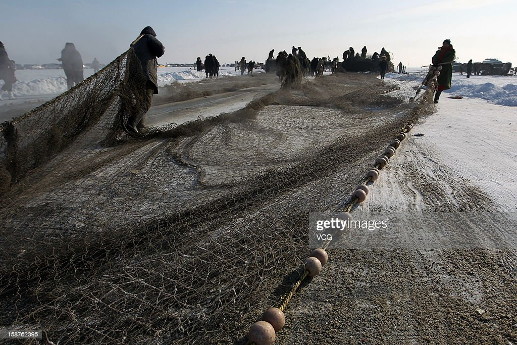 Fishermen pull a net after about 10 hours fishing on the frozen Chagan Lake on December 27, 2012 in Songyuan, China. Traditional winter fishing in the Chagan Lake, the biggest freshwater lake in Jilin province, kicked off on Thursday. It usually lasts about two months and has been popular for more than 1,000 years.