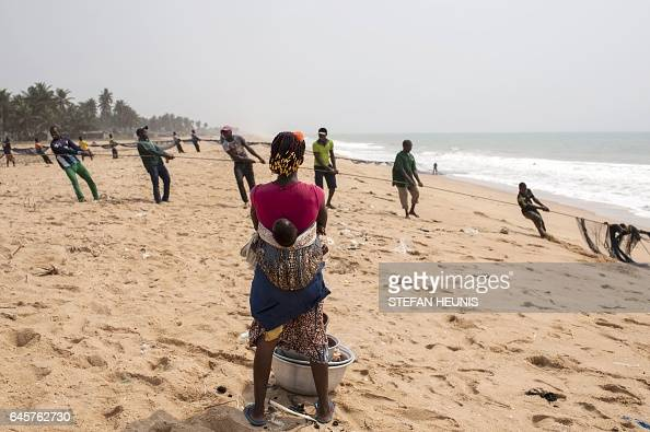 Fishermen pull their nets on January 11 2017 on a beach outside the small coastal town of Ouidah some 40km from Cotonou With its beaches a remarkable...