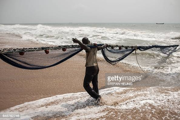 TOPSHOT Fishermen pull their nets on January 11 2017 on a beach outside the small coastal town of Ouidah some 40km from Cotonou With its beaches a...
