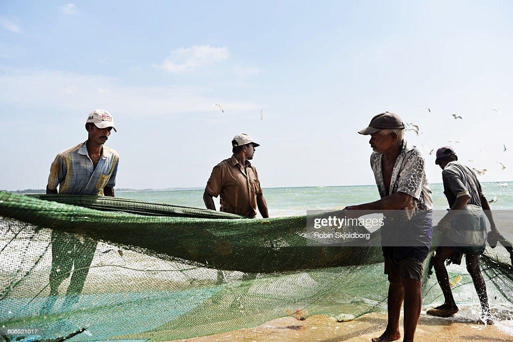 Fishermen pulling in fishing net from beach