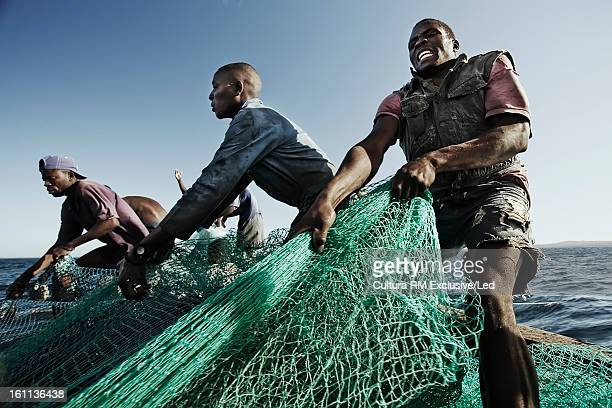 Fishermen pulling in net in water