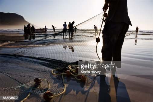 Fishermen pulling their catch onto the beach. : Bildbanksbilder