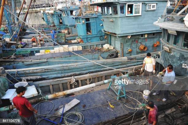 Fishermen repair vessels at a fishing port on August 30 2017 in Qingdao Shandong Province of China Fishing ban started from May 1 on China's Yellow...