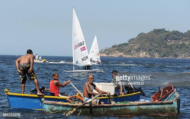 Fishermen row as sailing boats compete in the International Sailing Regatta held in the Guanabara Bay in Rio de Janeiro Brazil on 15 August 2015 an...