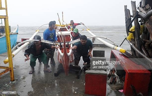 Fishermen secure fishing outrigger boats to higher grounds along the coastal area of Manila Bay on October 18 after the Philippine coast guard banned...