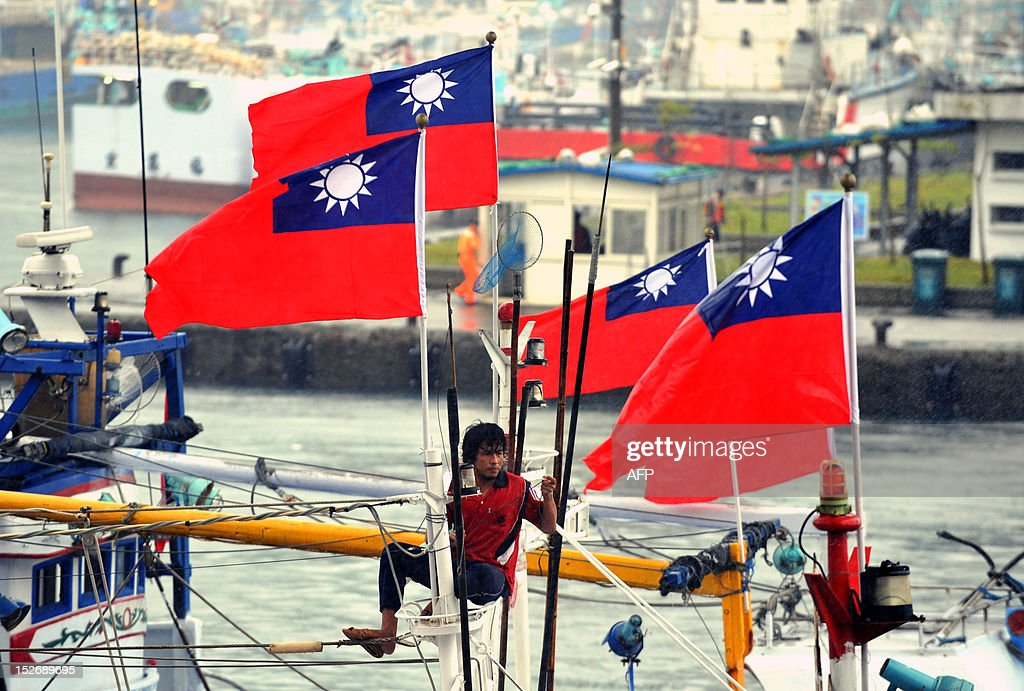 A fishermen secures flags on fishing boat as it leaves Suao, to head to the disputed East China Sea islands, known as Senkaku in Japanese and Diaoyu Islands in Chinese, on September 24, 2012. Dozens of Taiwanese fishing boats will set sail for disputed East China Sea islands, organisers said, amid a row over territory controlled by Japan but also claimed by China and Taiwan. AFP PHOTO / Mandy CHENG