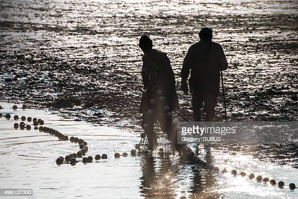 Fishermen silhouette fishing with net in french pond water