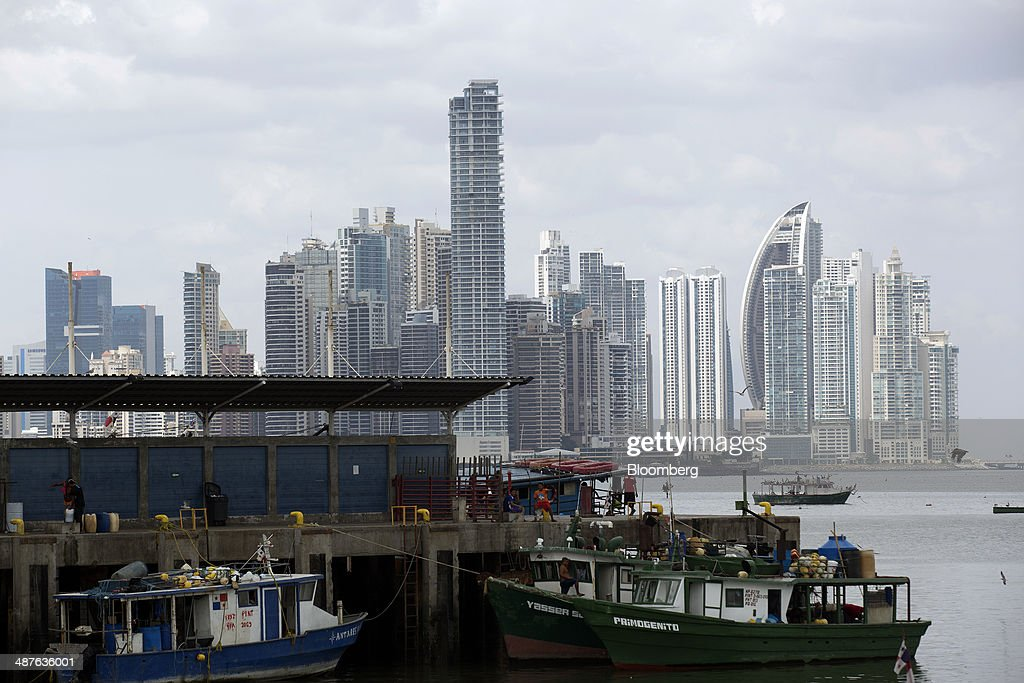 Fishermen sit at the dock beside the fish market as buildings stand in the skyline in the background in Panama City, Panama, on Wednesday, April 23, 2014. Panama has averaged about 9 percent economic growth annually since 2008 and unemployment levels hover near a record low of 4.1 percent. Photographer: Susana Gonzalez/Bloomberg via Getty Images