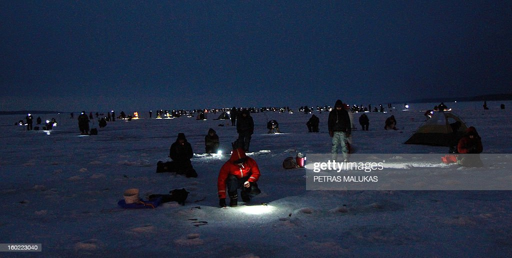 Fishermen sit on the frozen surface of the Kursiai Lagoon near Klaipeda, Lithuania, to catch smelts on January 27, 2013. Several thousands of amateur fishermen from all over Lithuania gather on the ice to catch the small fish.