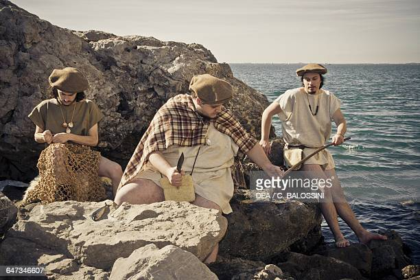 Fishermen sitting on rocks mending nets and fishing Illyrian civilisation mid3rd century BC Historical reenactment