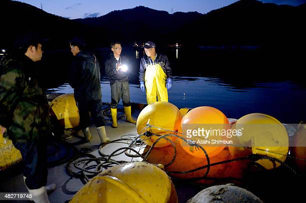 Fishermen tie their fishing equipments with ropes as the tsunami warning is issued on April 3 2014 in Ishinomaki Miyagi Japan A 60centimeter tsunami...
