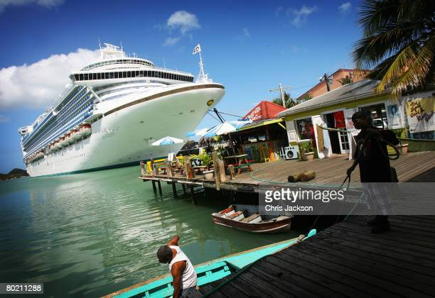 Fishermen tie up their wooden boat next to a cruise liner in St John's Harbour on March 10 2008 in St John's Antigua In high season up to five cruise...