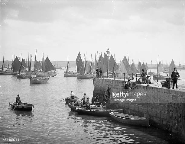Fishermen unload their catches Falmouth Pier Falmouth Cornwall c1860c1922 with boats moored in the background