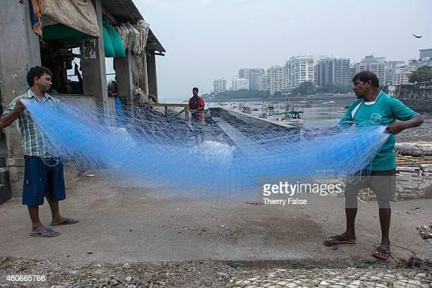 Fishermen untangle a net on a Mumbai beach
