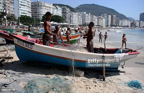 Fishermen untangle a net on their boat at Copacabana beach in Rio de Janeiro Brazil on March 29 2015 AFP PHOTO / YASUYOSHI CHIBA / AFP / YASUYOSHI...