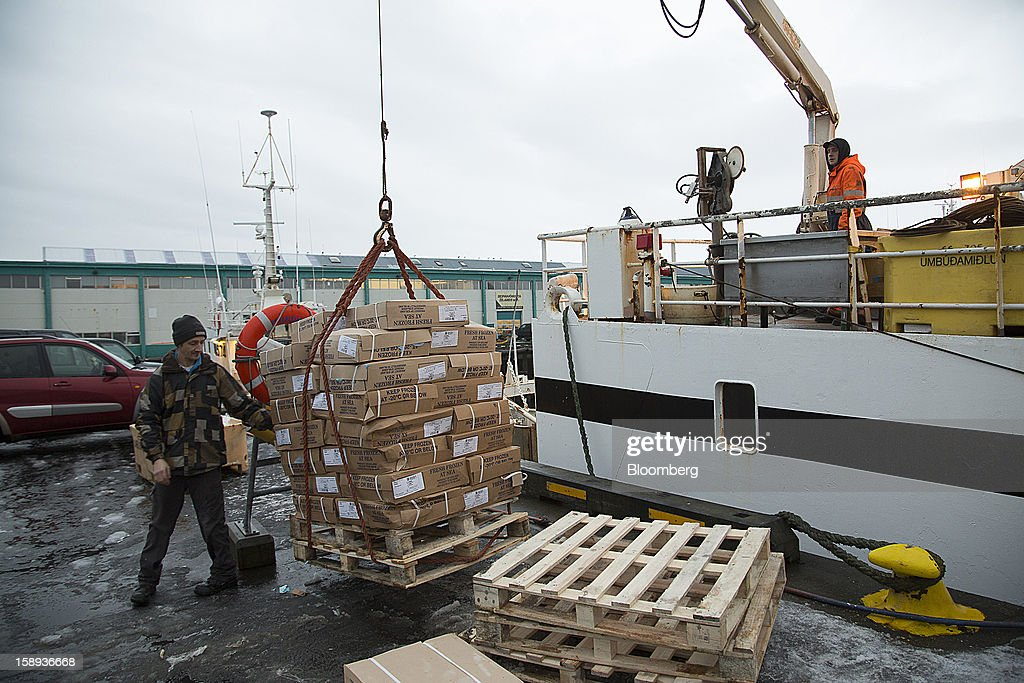 Fishermen use a crane to offload boxes of fresh frozen fish from a commercial fishing vessel at the harbor in Reykjavik, Iceland, on Wednesday, Jan. 2, 2013. Iceland's inflation rate eased in December as central bank efforts to stabilize the krona with interest rate increases paid off. Photographer: Arnaldur Halldorsson/Bloomberg via Getty Images