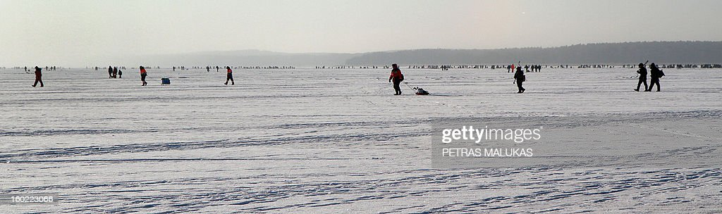 Fishermen walk over the frozen surface of the Kursiai Lagoon near Klaipeda, Lithuania, to catch smelts on January 27, 2013. Several thousands of amateur fishermen from all over Lithuania gather on the ice to catch the small fish.