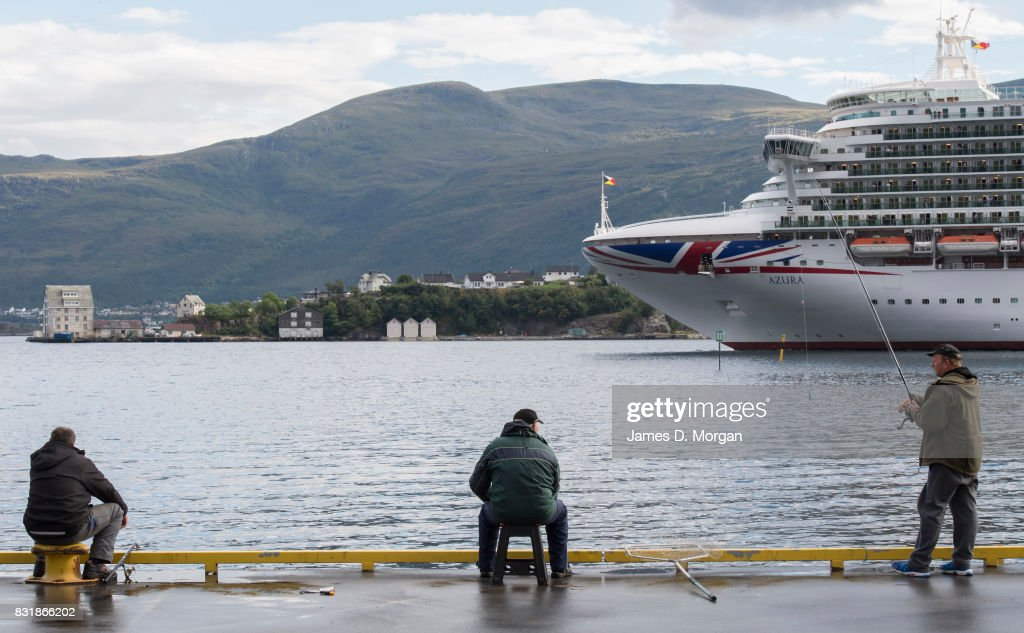 Fishermen watch as P&O Cruises Azura departs port on August 15, 2017 in Alesund, Norway. With over 3000 guests and 1200 crew, the 115,000 tonne ship is on a seven day Norweigian fjord cruise from Southamton arriving back on the 19th August 2017. Summer is a popular time for the Norweigan Fjord cruise industry with dozens of cruise ships in the waters off Norway with tens of thousands of visitors disembarking every day.