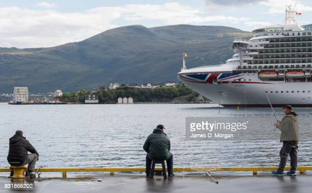 Fishermen watch as PO Cruises Azura departs port on August 15 2017 in Alesund Norway With over 3000 guests and 1200 crew the 115000 tonne ship is on...