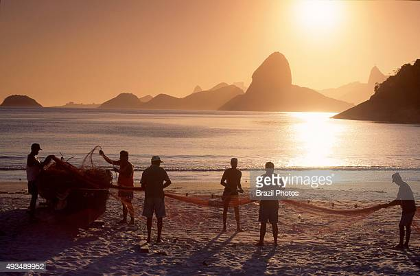 Fishermen work in Niterói with a nice view of Rio de Janeiro mountains including Sugar Loaf and Corcovado Brazil
