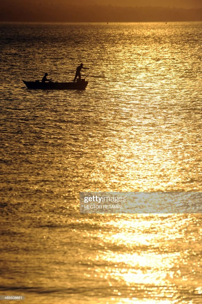 Fishermen work on a small boat near the wharf Jeremie, in La Saline neighborhood, in Port au Prince, on January 27, 2013. AFP PHOTO/Hector RETAMAL